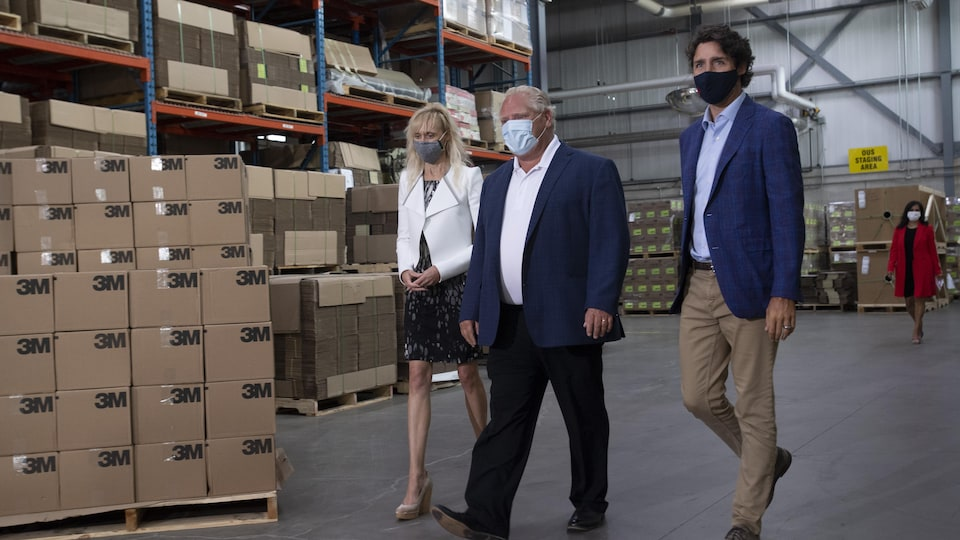 Justin Trudeau, Doug Ford et Penny Wise marchent à l'intérieur de l'entrepôt de l'usine 3M de Brockville, en Ontario. Chacun porte un masque de protection.