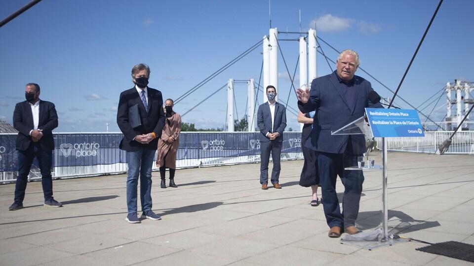 Doug Ford a dévoilé les plans de revitalisation de la Place de l'Ontario lors d'un point de presse le 30 juin. Il parle devant un lutrin, à côté du maire de Toronto.