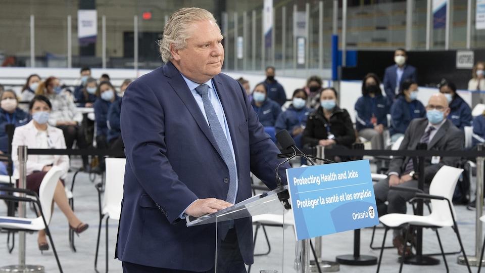 Le premier ministre Doug Ford écoute une question lors d'une conférence de presse à un aréna transformé en centre de vaccination à Toronto.