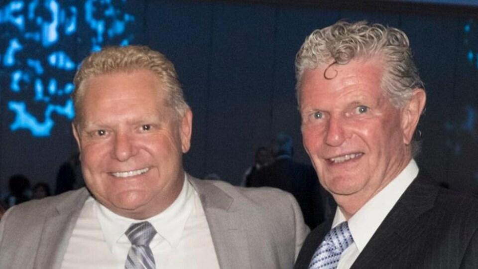 Doug Ford et Ron Taverner se tiennent bras dessus bras dessous.