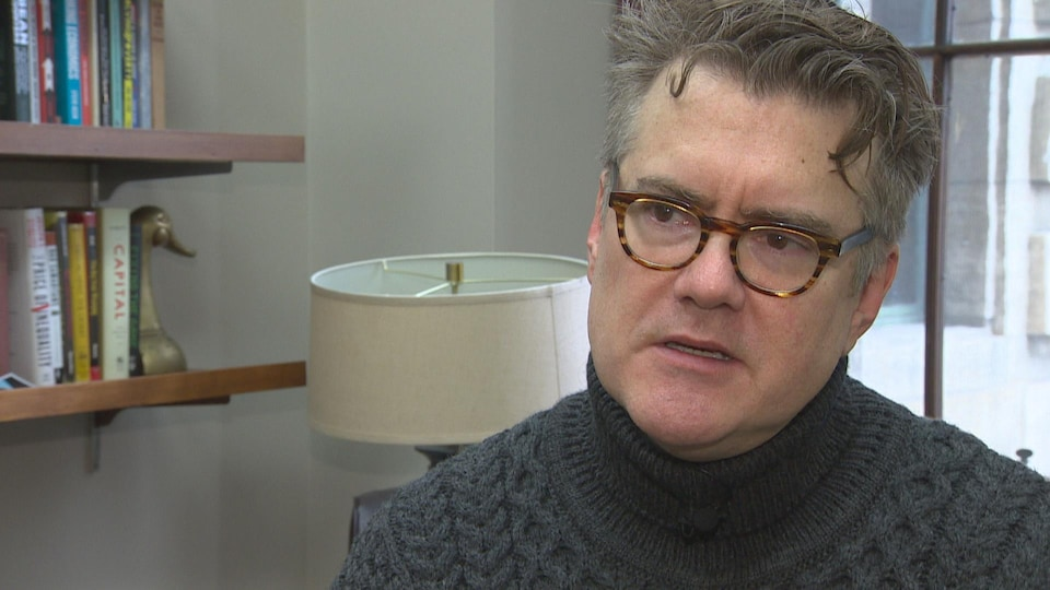 Gros plan sur Dougald Lamont, dans son bureau, vêtu d'un col roulé gris. Au fond, une lampe et des livres.
