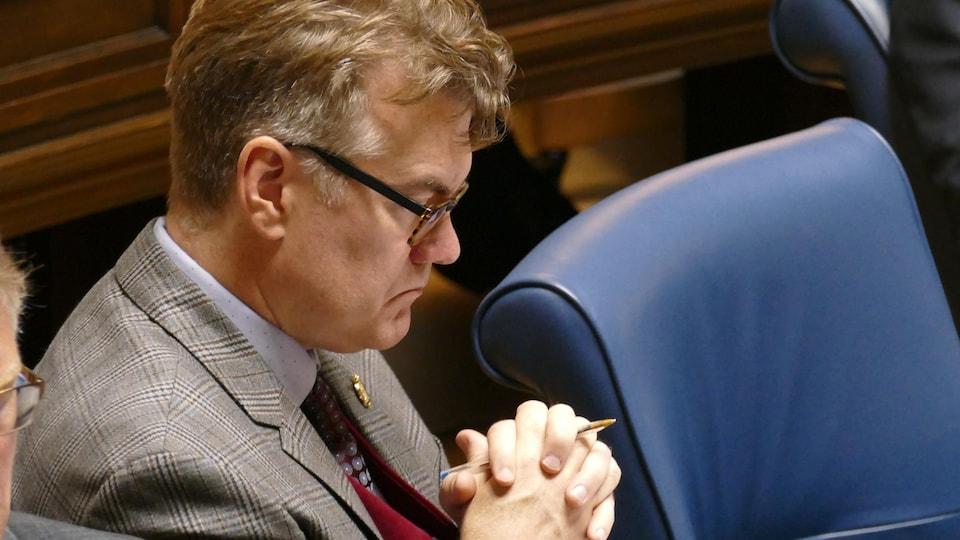 Gros plan sur Dougald Lamont, de profil, assis à son pupitre de député, les mains croisées.