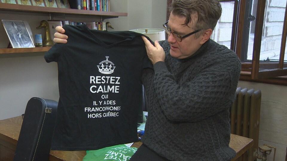 Dougald Lamont, assis sur le coin de son bureau, montre un T-shirt noir avec l'inscription «Restez calmes, oui il y a des francophones hors Québec».