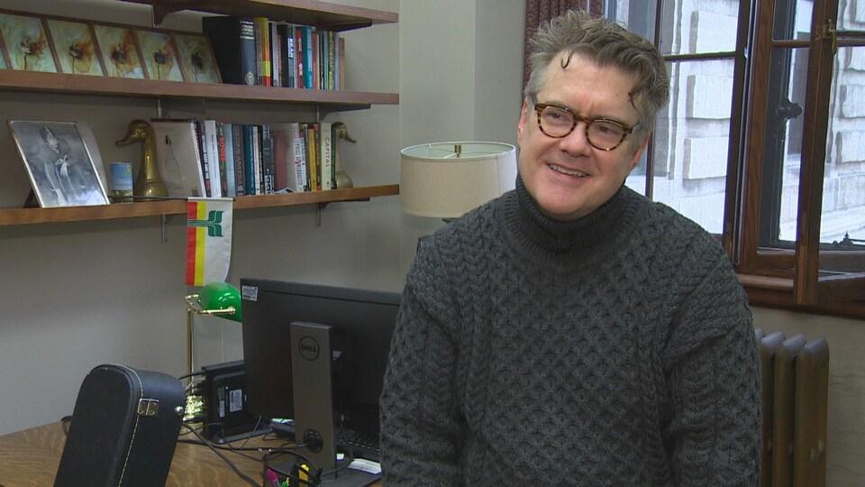 Dougald Lamont, assis sur son bureau, souriant. Au fond, on voit des étagères de livre et un drapeau franco-manitobain.