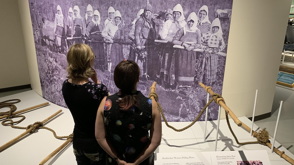 Deux visiteurs regardent l'exposition The Doukhobor Living Book Project: 120 Years in Saskatchewan au Western Devloppement Museum de Saskatoon.