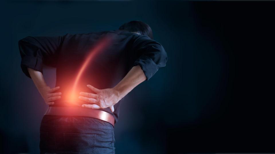 Un homme se tient le dos.