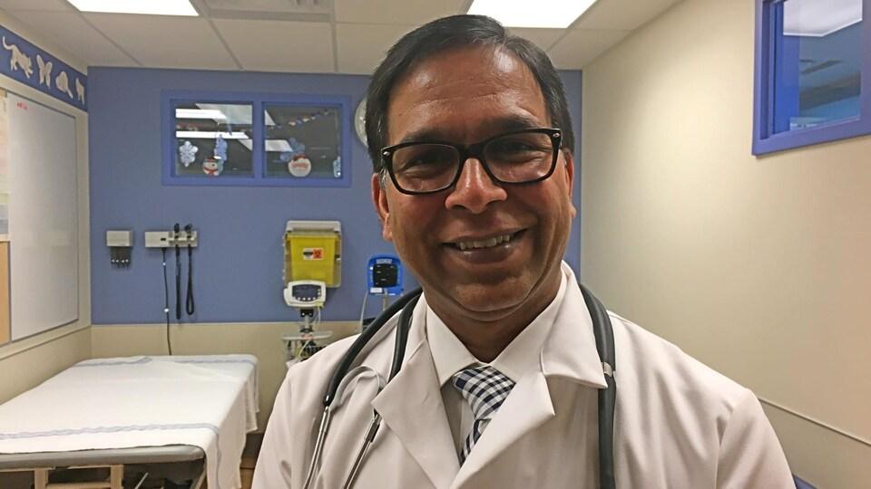 Un docteur en blouse blanche porte un stéthoscope autour du cou. Il pose, tout sourire, dans une salle d'examen d'un hôpital.
