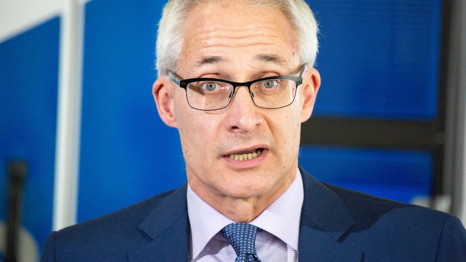 Un homme dans un complet bleu parle en conférence de presse.