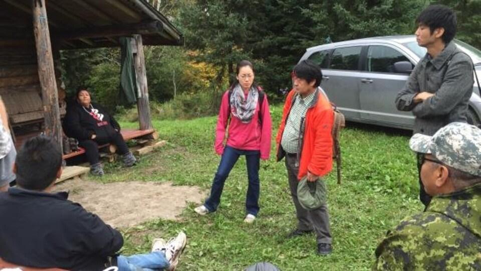 De jeunes autochtones qui discutent ensemble devant une résidence.