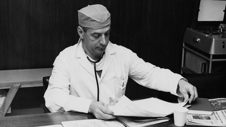 Le Dr Pierre Grondin, en tenue médicale, consultant des dossiers.