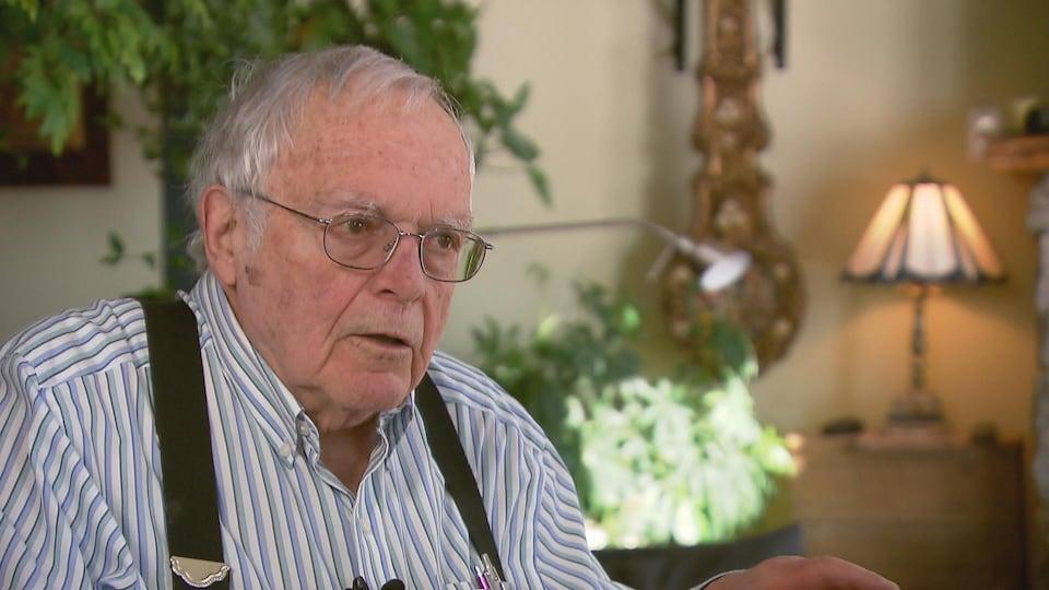 Un homme âgé assis dans un salon.