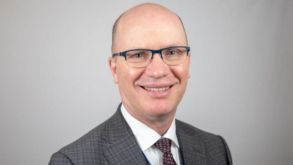 La photo d'un homme chauve qui porte des lunettes.