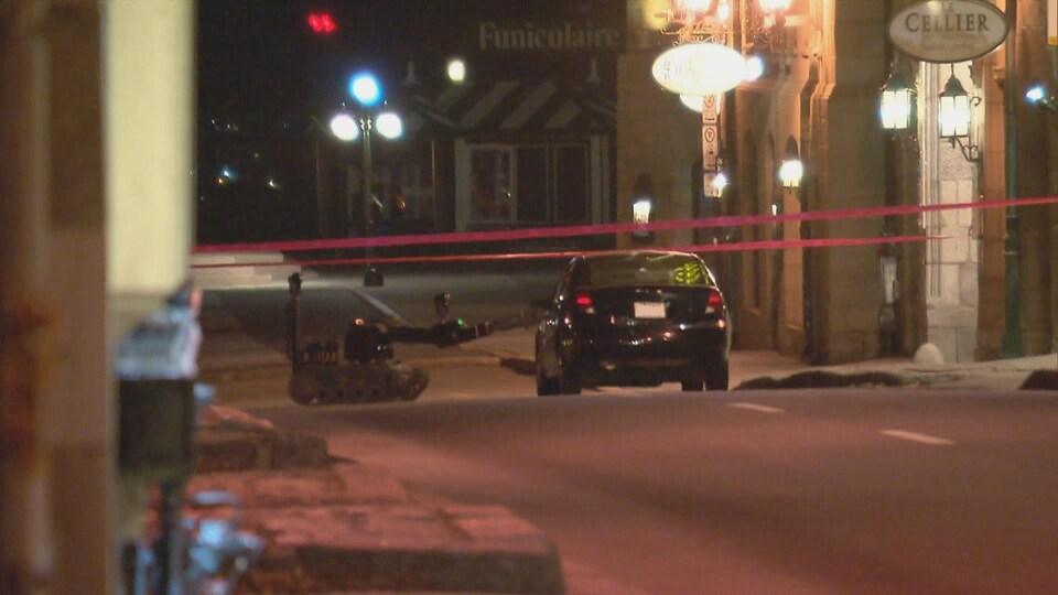 Un robot artificier s'approche du véhicule noir du suspect.