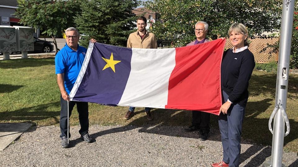 Quatre personnes tiennent un drapeau.