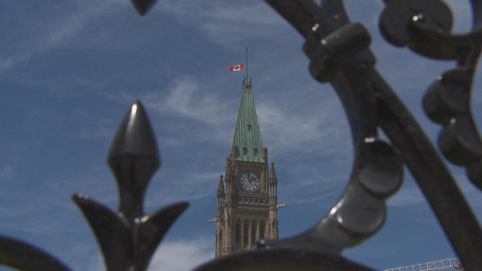 Un drapeau du Canada se trouve à mi-hauteur de son mât, au sommet de la tour de la Paix du parlement d'Ottawa.