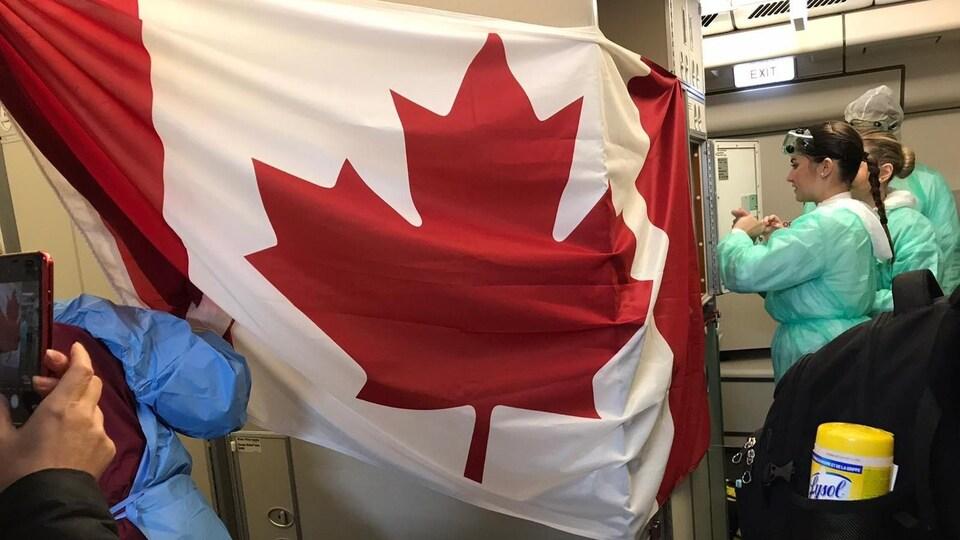 Un drapeau du Canada orne l'un des murs de l'avion. Des femmes en tuniques et lunettes s'activent.