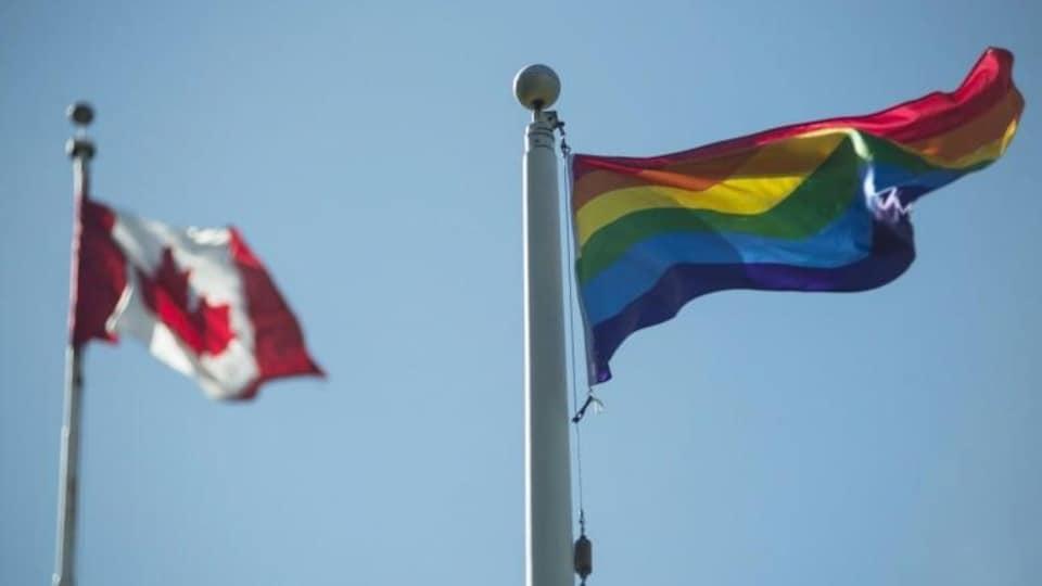 Vue du drapeau de la Fierté et du drapeau du Canada qui flottent.