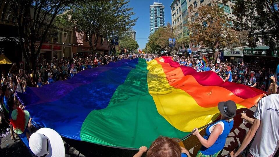 Un immense drapeau de la fierté est porté dans les rues du quartier West End, à Vancouver, lors d'un défilé.