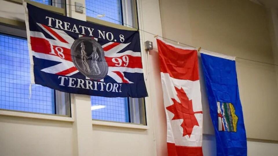 On voit le drapeau du Traité no 8 sur un mur, à côté de celui du Canada et de celui de l'Alberta.
