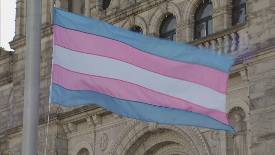 Le drapeau de la fierté transgenre flotte devant la façade d'un bâtiment.