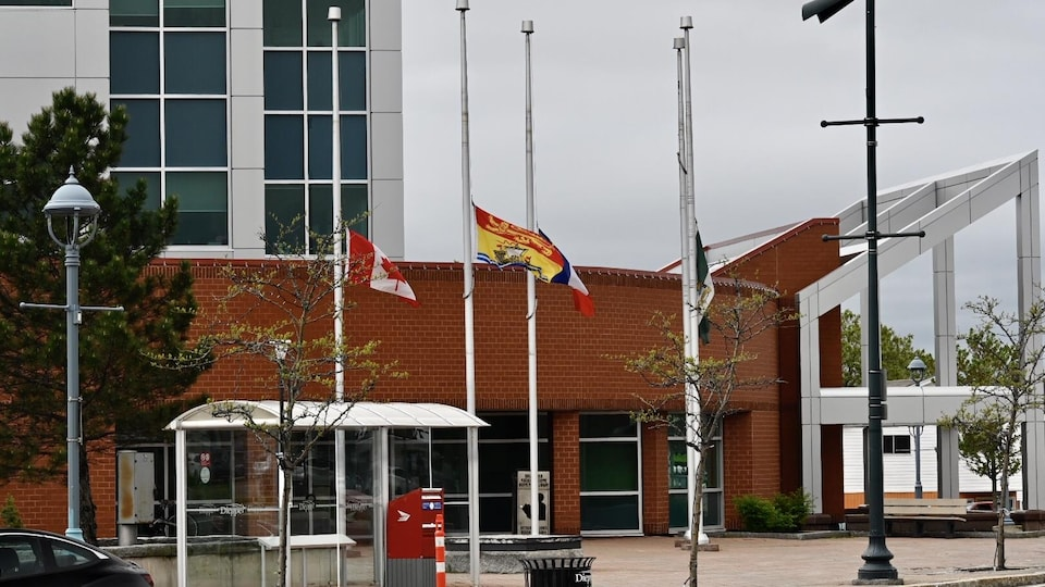 Les drapeaux sont en berne devant l'hôtel de ville de Dieppe au Nouveau-Brunswick.