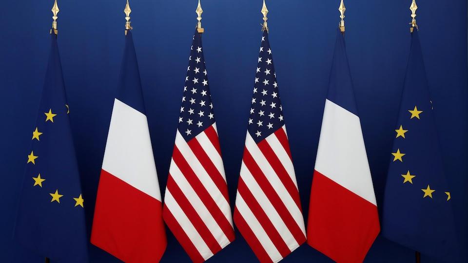 Des drapeaux de l'Union européenne, de la France et des États-Unis.