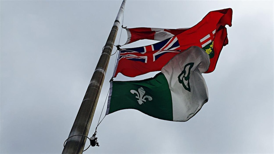 Le drapeau franco-ontarien, hissé en haut d'un mât aux côtés de ceux de l'Ontario et du Canada.