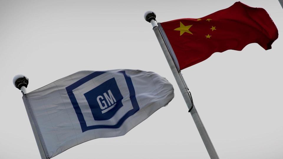 Les drapeaux de General Motors et de la Chine flottent dans le vent.