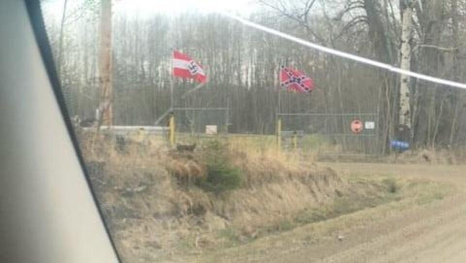 Deux drapeaux flottent à l'entrée d'une propriété, au loin.