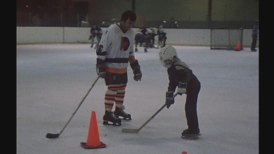 Un joueur des Draveurs observe un enfant s'exercer au hockey.