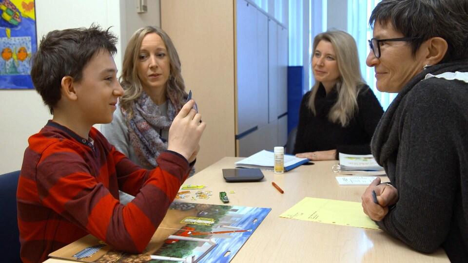 On voit les quatre personnes assises à une table. Les trois femme regardent Florent.