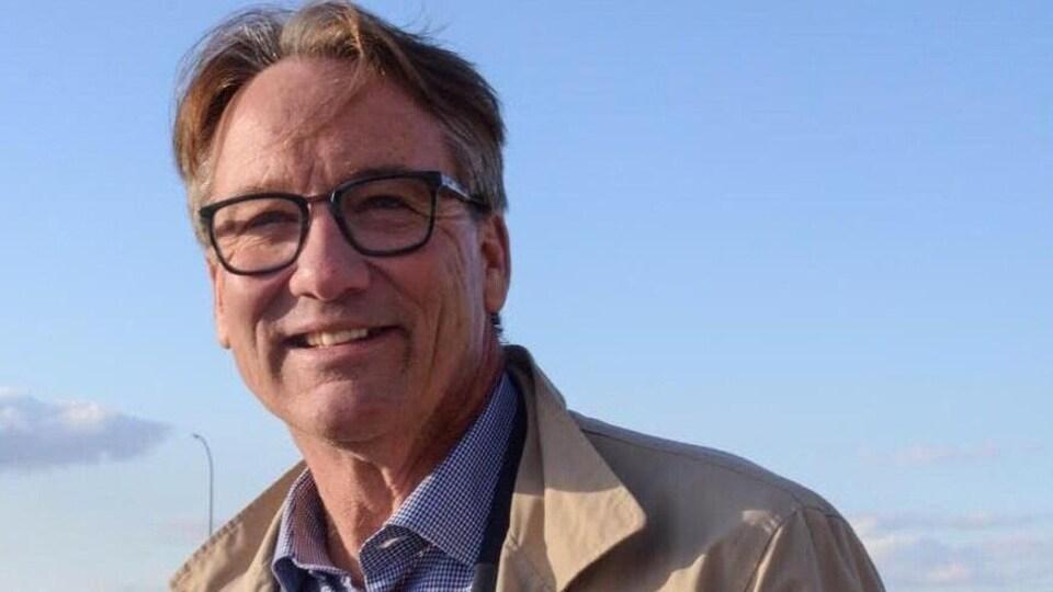 Un homme portant des lunettes à l'extérieur.