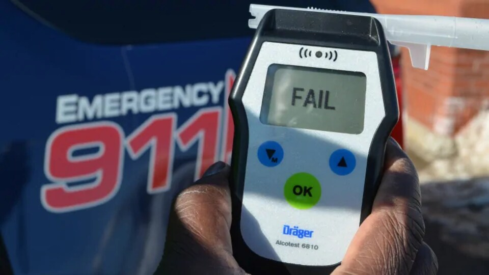 Une main tient un appareil de détection de drogue utilisé par les policiers lors de contrôles routiers