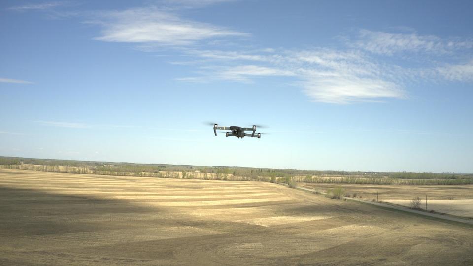 Un drone dans les airs au-dessus de champs.