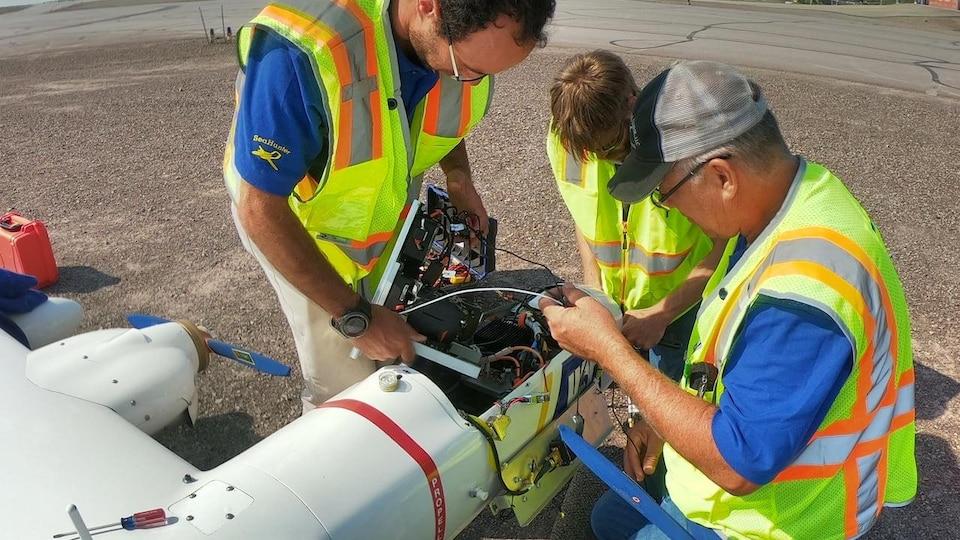 Trois hommes examinent l'intérieur d'un drone.