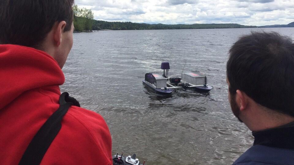 Deux étudiants sont sur le bord d'un lac et naviguent leur drone
