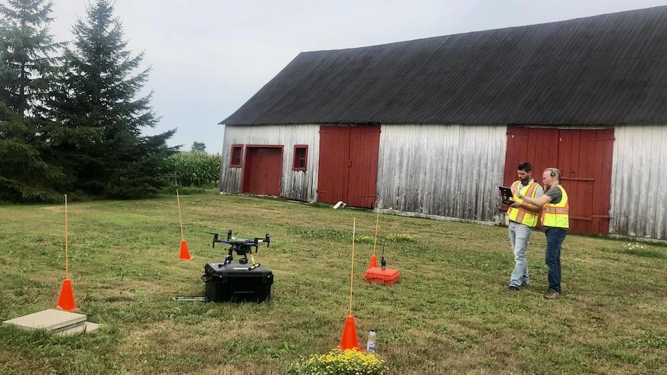 Deux hommes qui portent un dossard jaune fluo manient un drone conçu pour la recherche et sauvetage.
