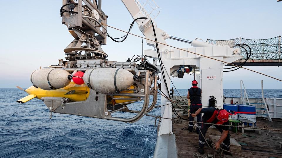 Des marins hissent un drone sous-marin à l'aide d'une grue.