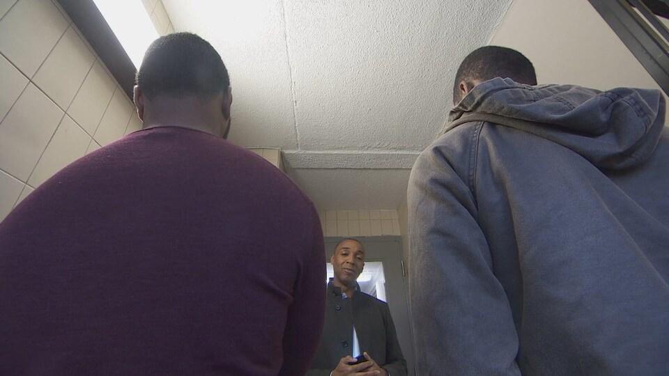 Deux jeunes hommes de dos devant le journaliste de CBC News.