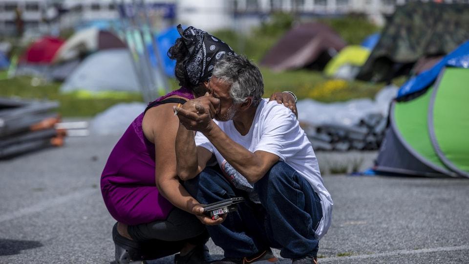 Une personne sans-abri pleure et est consolée par quelqu'un durant le démantèlement du campement au parc Crab, à Vancouver.