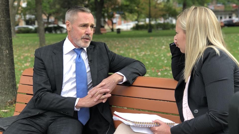 Un homme en complet veston et cravate répond aux questions d'une journaliste.