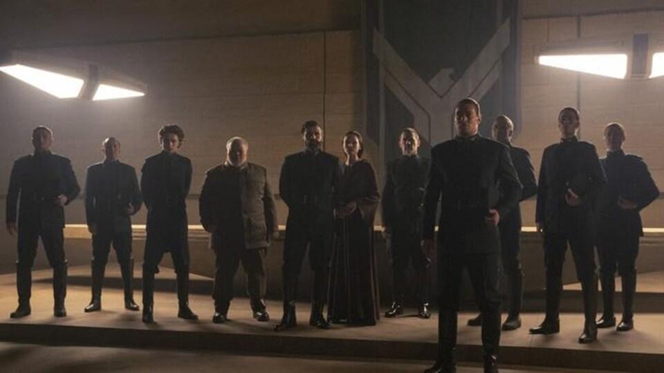 Une dizaine de personnes habillées en noir se tiennent debout.