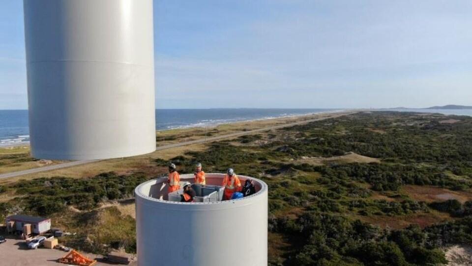 Photo aérienne d'une équipe se trouvant dans une section de tour d'éolienne, alors qu'une section du mat soulevée par une grue s'apprête à être mise en place.