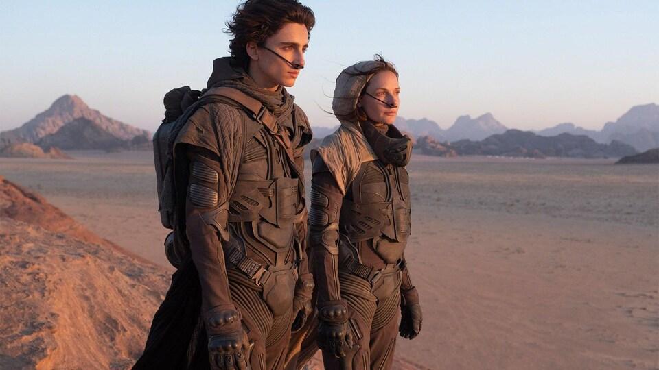 Un homme et une femme debout dans le désert avec des fils dans le nez.
