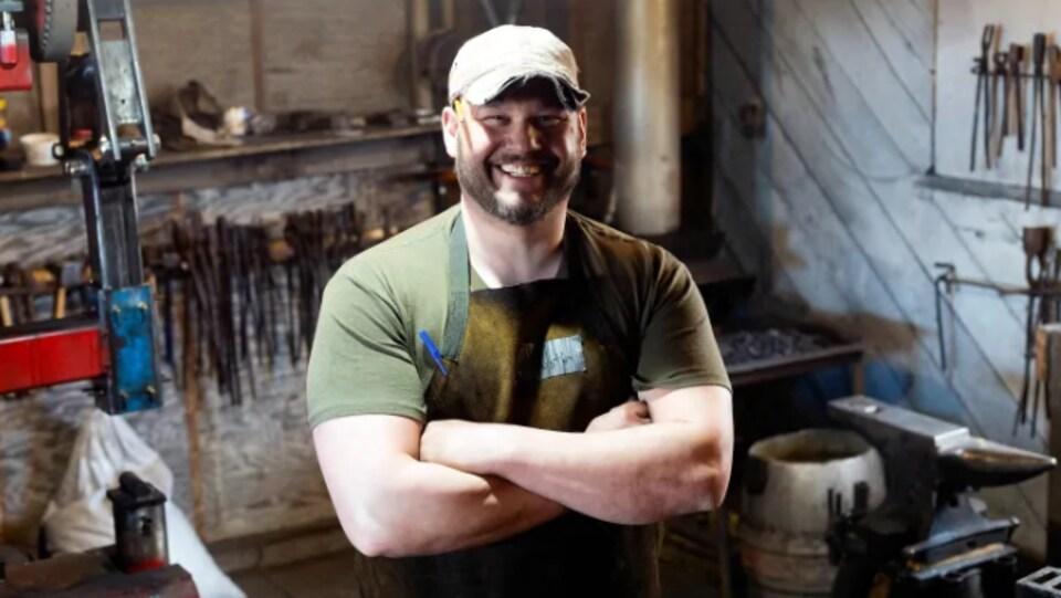 Dustin Small sourit. il porte une casquette et se trouve dans la forge qu'il a bâtie.