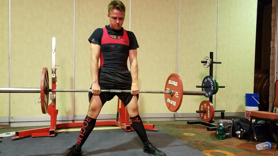 Un homme soulève une barre avec des poids aux extrémités.