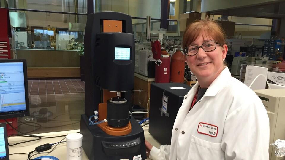 Isabelle Germain dans son laboratoire portant un sarrau blanc.