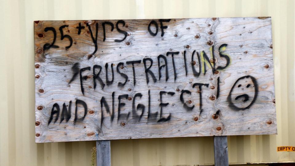 Un panneau avec l'inscription : plus de 25 ans de frustrations et de négligences.