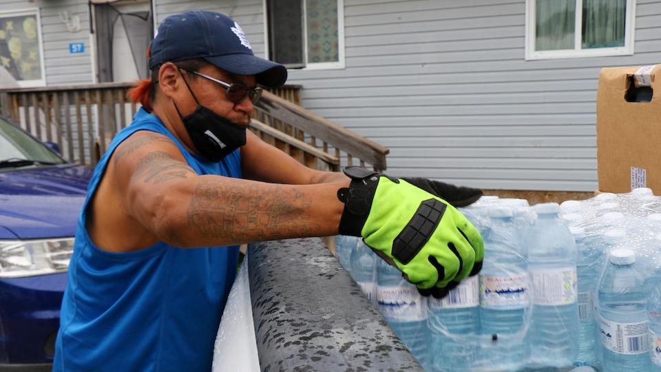 Un homme sort des bouteilles d'eau du coffre ouvert de son auto.