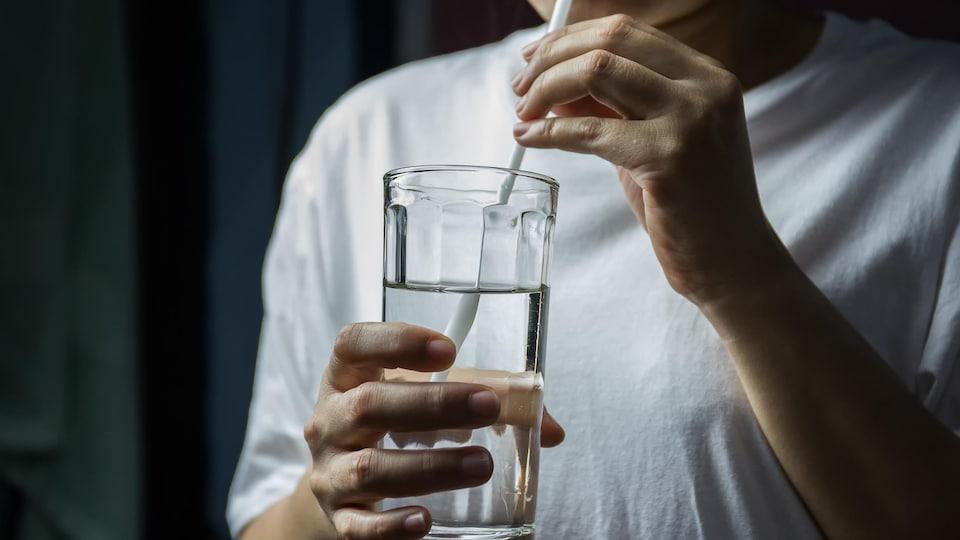 Une personne buvant de l'eau dans un verre à l'aide d'une paille.